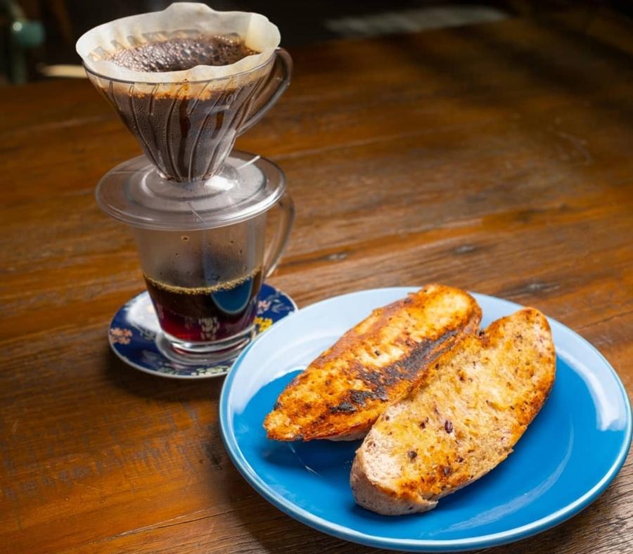 Foto do café coado da Fazenda Irarema acompanhado de um pão na chapa em um prato azul