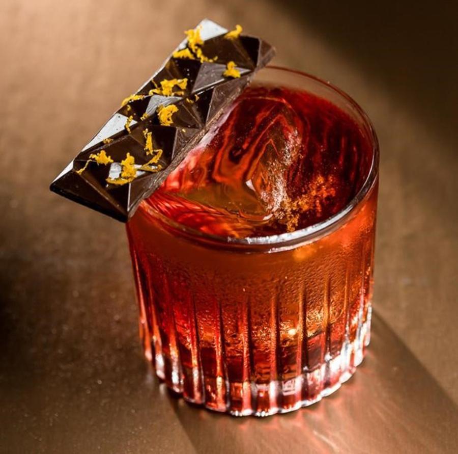Foto do Drink Boulevadier do Olivio Bar, que leva ainda um pedaço de chocolate