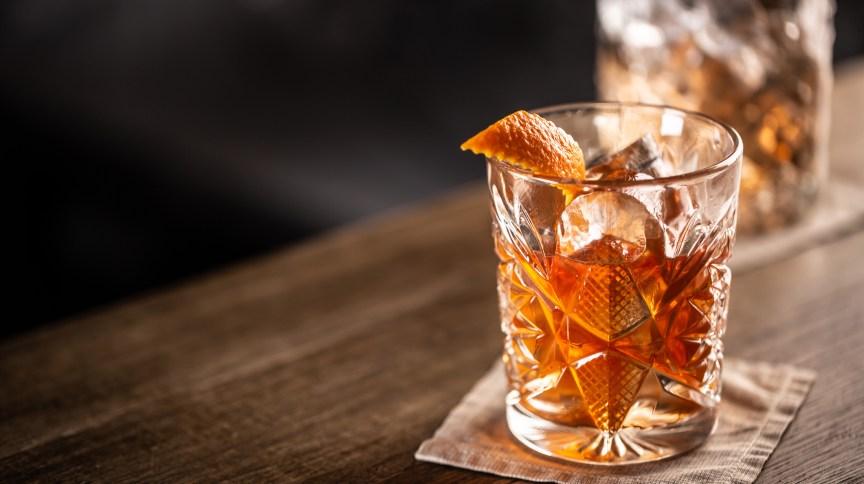 Old fashioned whiskey drink on ice with orange zest garnish.