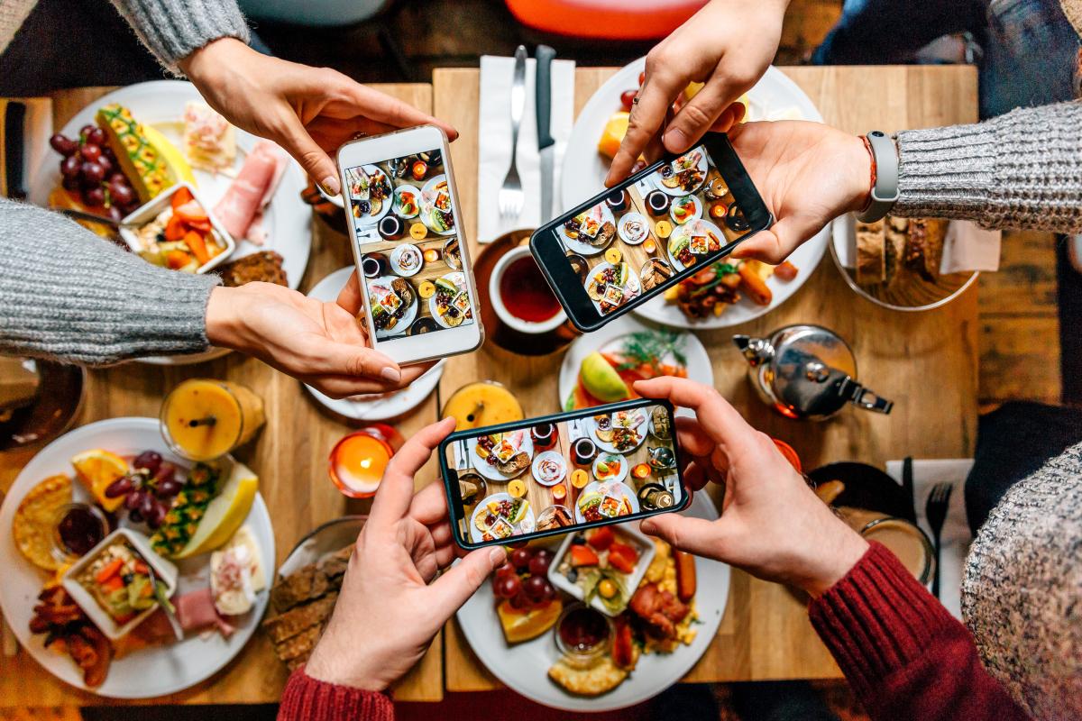 Amigos tirando fotos da comida na mesa com smartphones durante o brunch em um restaurante