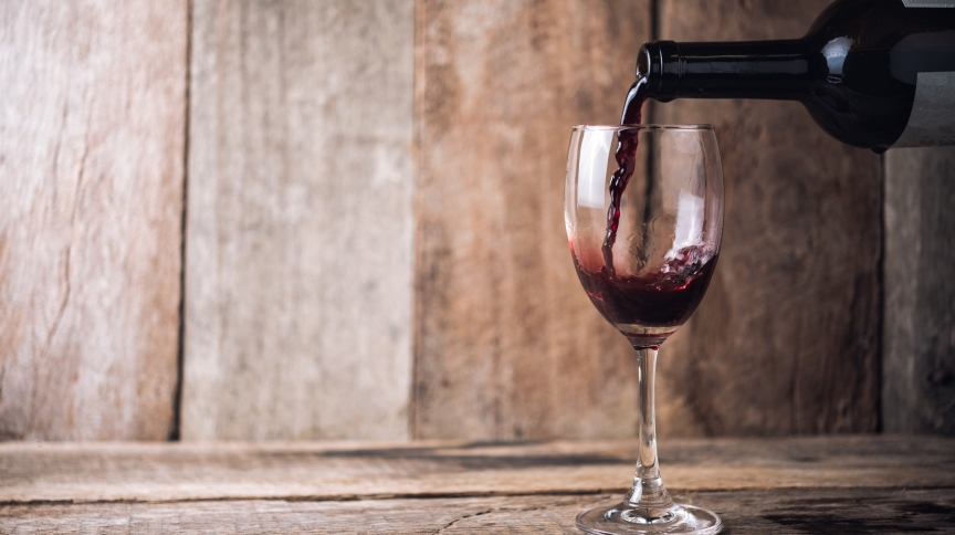 pouring wine into glass on wood background