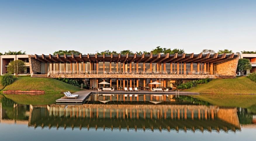 Detalhes da fachada do Fasano Boa Vista, com quartos, restaurante e deck de madeira com vista para o lago